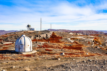 Metal bunker with meteorologic station and autumn greenlandic orange tundra landscape with mountains in the background, Kangerlussuaq, Greenland