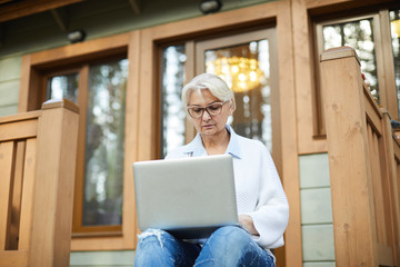 Serious mature woman with laptop sitting on terrace and searching for data in the net