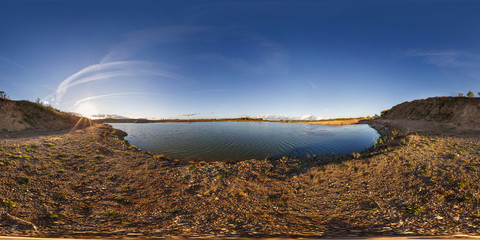 full seamless panorama 360 angle view near quarry flooded with water for sand extraction mining in the evening sun in equirectangular spherical equidistant projection for VR AR content