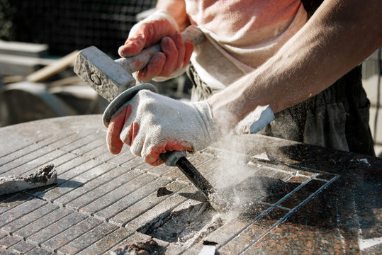 Stone carver in gloves working with a hammer and chisel on a marble slab. heavy handwork. production of monuments from marble. working with natural stone