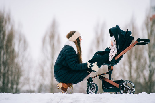 Fashionable stylish young mother rest with her daughter sitting in stroller in park outdoor at winter. Motherhood happiness. Children - flowers of life.  Beautiful girl with her baby winter portrait.