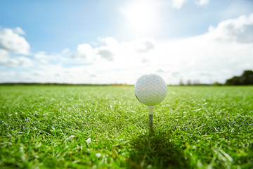 White golf ball on tee on vast green play field with cloudy sky and sunshine above