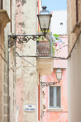 Specchia, Apulia - Lanterns and a balcony in a historic alleyway