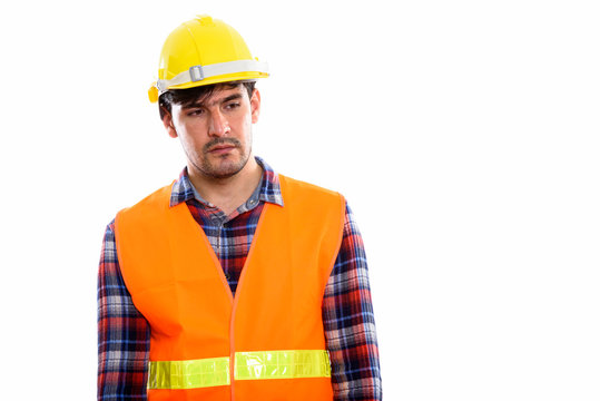 Young Persian man construction worker thinking while looking sad