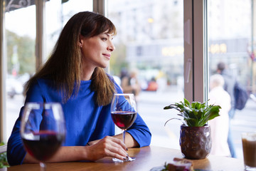 Beautiful woman drinking red wine with friends in restaurant, portrait with wine glass near window. Vocation holidays bar concept..