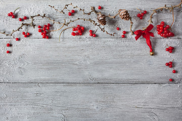 Christmas wood background, twigs, cones, red berries and bell