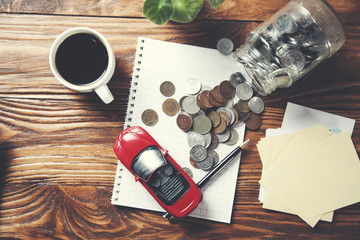 coins in glass jar with car model