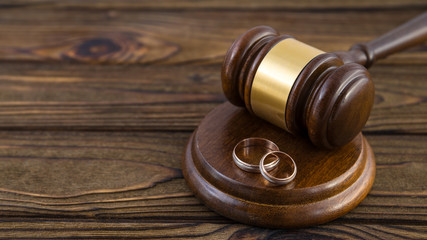 Wedding rings, hammer of the judge on a wooden background. The Divorce Process