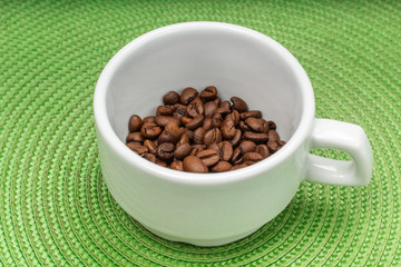 white cup of grain coffee on a saucer, green circle background