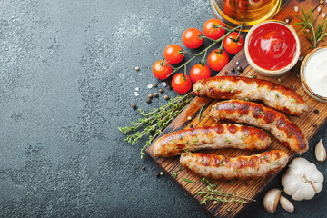 Fried sausages with sauces and herbs on a wooden serving Board. Great beer snack on a dark background. Top view with copy space Wall mural