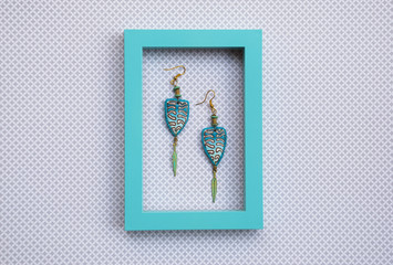 Long boho style earrings in white frame. Fashion jewelry background. Polymer clay jewellery.