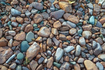 Multi colored beach stones on the shore of Lake Superior, background, texture