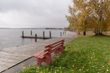 Red Park Bench and lake dock on a lake on misty cloudy Autumn day in October