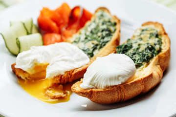 Whole wheat toasted croissant with arugula and poached egg, smoked salmon. Table arrengement side close-up view copy space