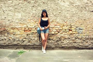 Beautiful young girl near the brick wall.