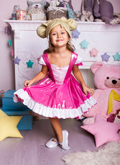 little girl in pink ballerina dress. kid christmas halloween costume. young happy girl with charming smile in white room is standing and dancing in pink fancy skirt and hat like hair