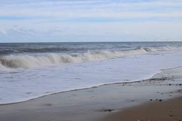 Landscape view of beautiful natural ocean scene looking out at tide, calm white foam of waves dash onto the sandy beach at Norfolk East Anglia England with blue skies and vast horizon