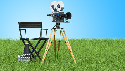 Cinema concept. Movie camera with film reels, chair, megaphone and clapperboard on the green grass against blue sky, 3D rendering