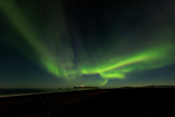 Bright green aurora borealis from Reynisfjara black sand beach in Iceland, looking towards the Dryholaey Peninsula and Lighthouse