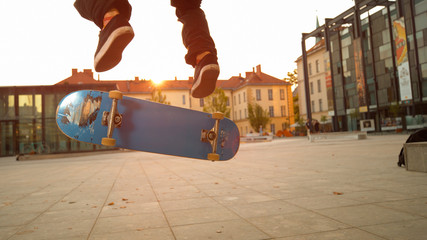 LOW ANGLE: Blue skateboard flipping underneath the young skateboarder's feet.