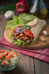 Doner kebab is lying on the cutting board. Shawarma with chicken meat, onions, salad lies on a dark old wooden table.