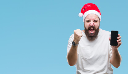 Young caucasian man wearing christmas hat showing smartphone screen over isolated background annoyed and frustrated shouting with anger, crazy and yelling with raised hand, anger concept