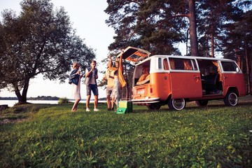 summer holidays, road trip, vacation, travel and people concept - smiling young hippie friends having fun over minivan car.