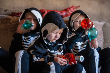 Happy children in carnival costumes, boys with a red crocodile in the garage. Black suit with the image of skeletons. Classic Halloween costume. Happy childhood of children