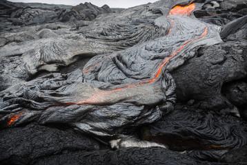 Molten magma breaking through the ground of the lava fields of Puu Oo, Big Island, Hawaii.
