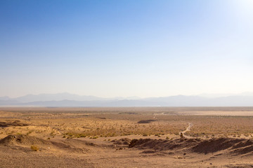Panorama of the Namak Salt lake, seen from above, with a road visible in the foreground and a valley in the background, in the afternoon, in Maranjab desert, near Kashan, in Iran.