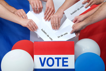 """Ballot box with VOTE on front and """"bulletin de vote"""" french for """"ballot"""" on envelopes being placed in ballot box french flag in background. Election voting concept for France"""
