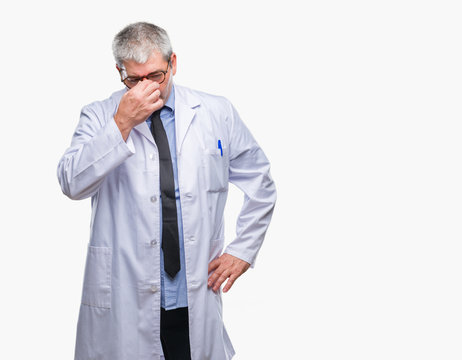 Handsome senior doctor, scientist professional man wearing white coat over isolated background tired rubbing nose and eyes feeling fatigue and headache. Stress and frustration concept.