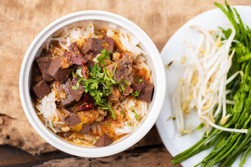 Northern Thai food (Kanom Jeen Nam Ngeaw) with vegetables on wooden background,spicy rice noodles soup