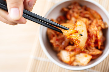 Hand holding chopsticks for eating kimchi cabbage in a bowl, Korean food