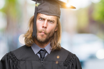 Young handsome graduated man with long hair over isolated background making fish face with lips, crazy and comical gesture. Funny expression.