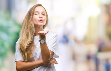 Young beautiful blonde woman wearing casual white t-shirt over isolated background looking at the camera blowing a kiss with hand on air being lovely and sexy. Love expression.