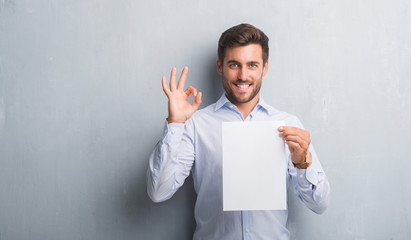 Handsome young man over grey grunge wall holding blank paper sheet contract doing ok sign with fingers, excellent symbol