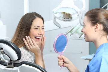Happy dentist patient checking whitening results