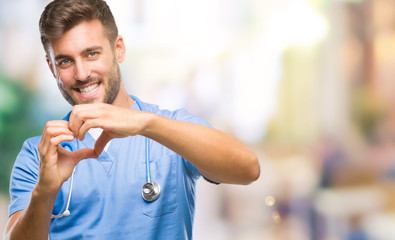 Young handsome doctor surgeon man over isolated background smiling in love showing heart symbol and shape with hands. Romantic concept.