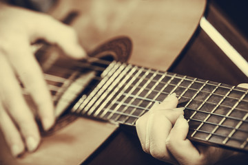 Closeup of man playing acoustic guitar