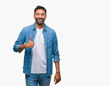 Adult hispanic man over isolated background doing happy thumbs up gesture with hand. Approving expression looking at the camera with showing success.