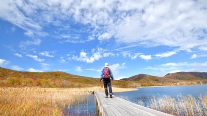 秋空と紅葉の草原を歩く