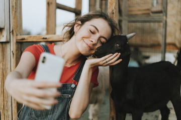 Happy girl taking a selfie with a black baby goat