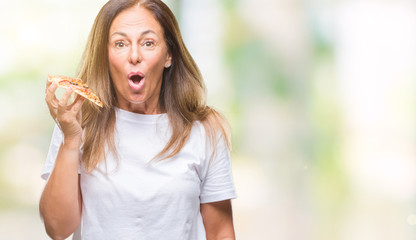 Middle age hispanic woman eating pizza slice over isolated background scared in shock with a surprise face, afraid and excited with fear expression