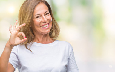 Middle age senior hispanic woman over isolated background smiling positive doing ok sign with hand and fingers. Successful expression.