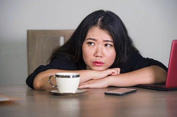 Asian Korean businesswoman working in stress at office computer desk feeling overwhelmed and frustrated suffering depression thinking looking away