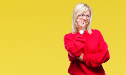 Young beautiful blonde woman wearing sweater and glasses over isolated background looking stressed and nervous with hands on mouth biting nails. Anxiety problem.