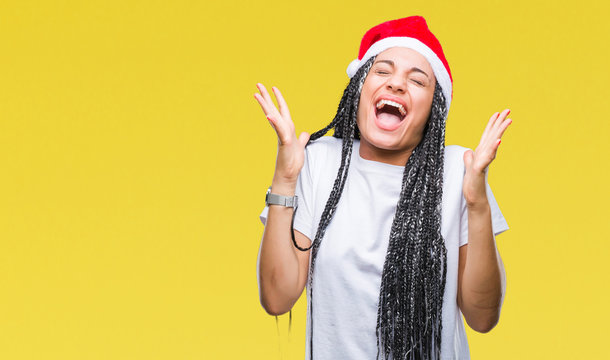 Young braided hair african american girl wearing christmas hat over isolated background celebrating crazy and amazed for success with arms raised and open eyes screaming excited. Winner concept