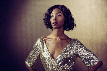Portrait of a beautiful woman in golden sequin dress waiting for her dreams