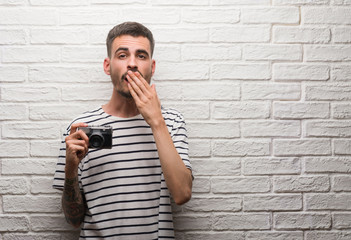 Young man holding vintage camera standing over white brick wall cover mouth with hand shocked with shame for mistake, expression of fear, scared in silence, secret concept